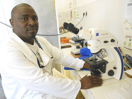 Mozambican health worker reading TB samples in a local health facility