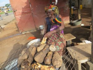 woman grilling yams holding child_Monagan_2013_CI-min